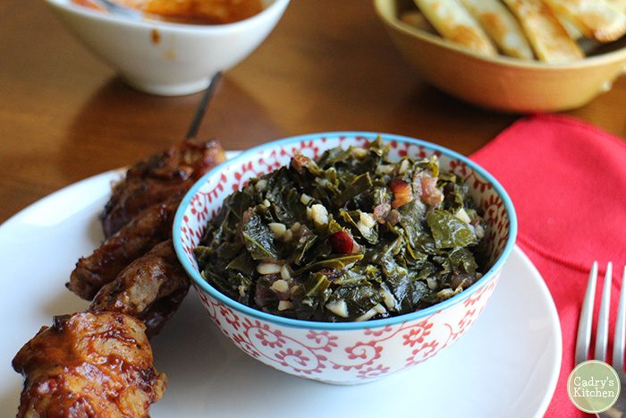Smoky sweet collard greens in bowl next to barbecued seitan skewer.
