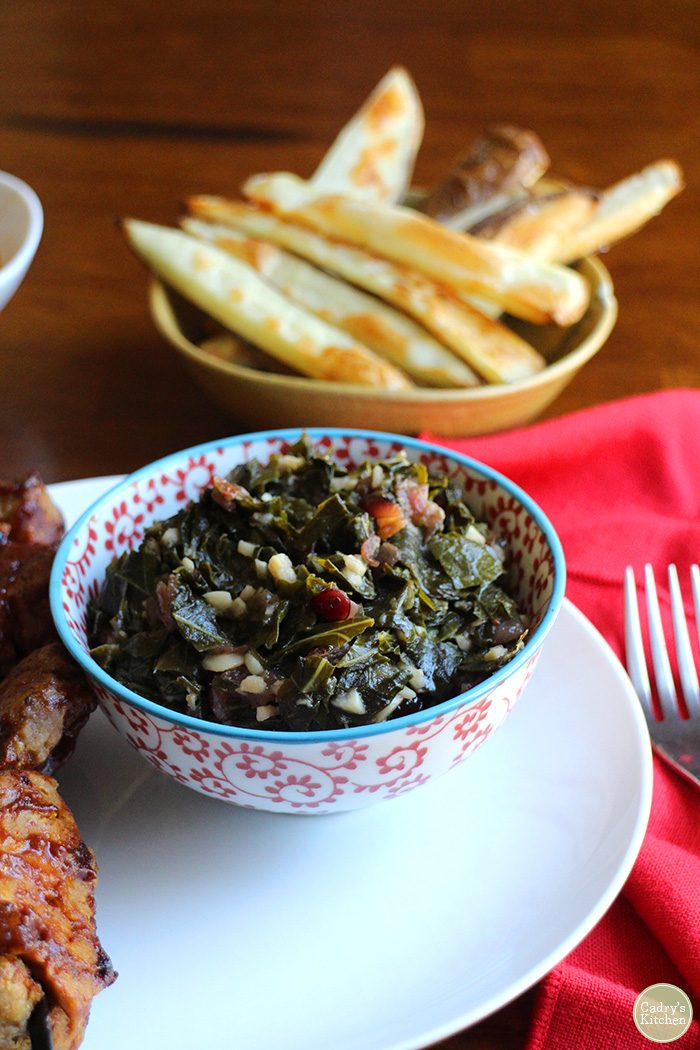 Smoky sweet vegan collard greens in bowl. French fries in background.