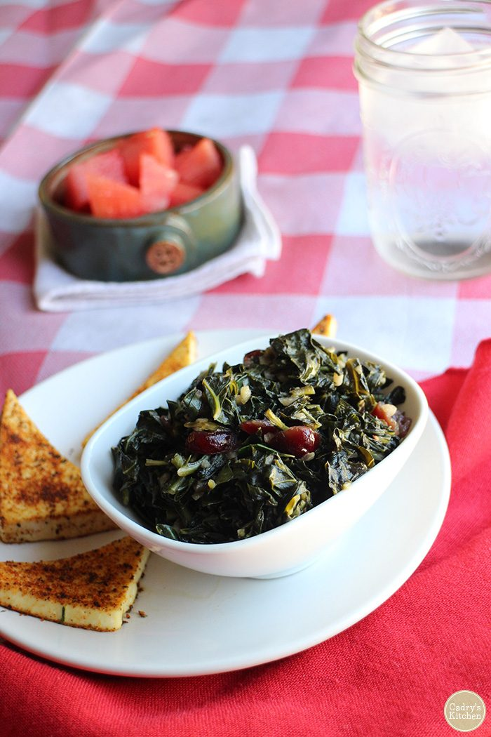 Smoky sweet vegan collard greens in bowl. Watermelon and water in background. Checkered tablecloth & red napkin on table.