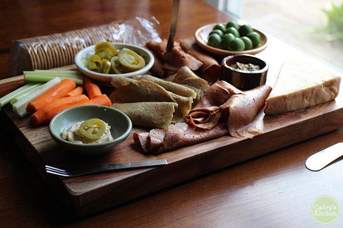 Herbivorous butcher deli slices, olives, and crudite on vegan cheeseboard.