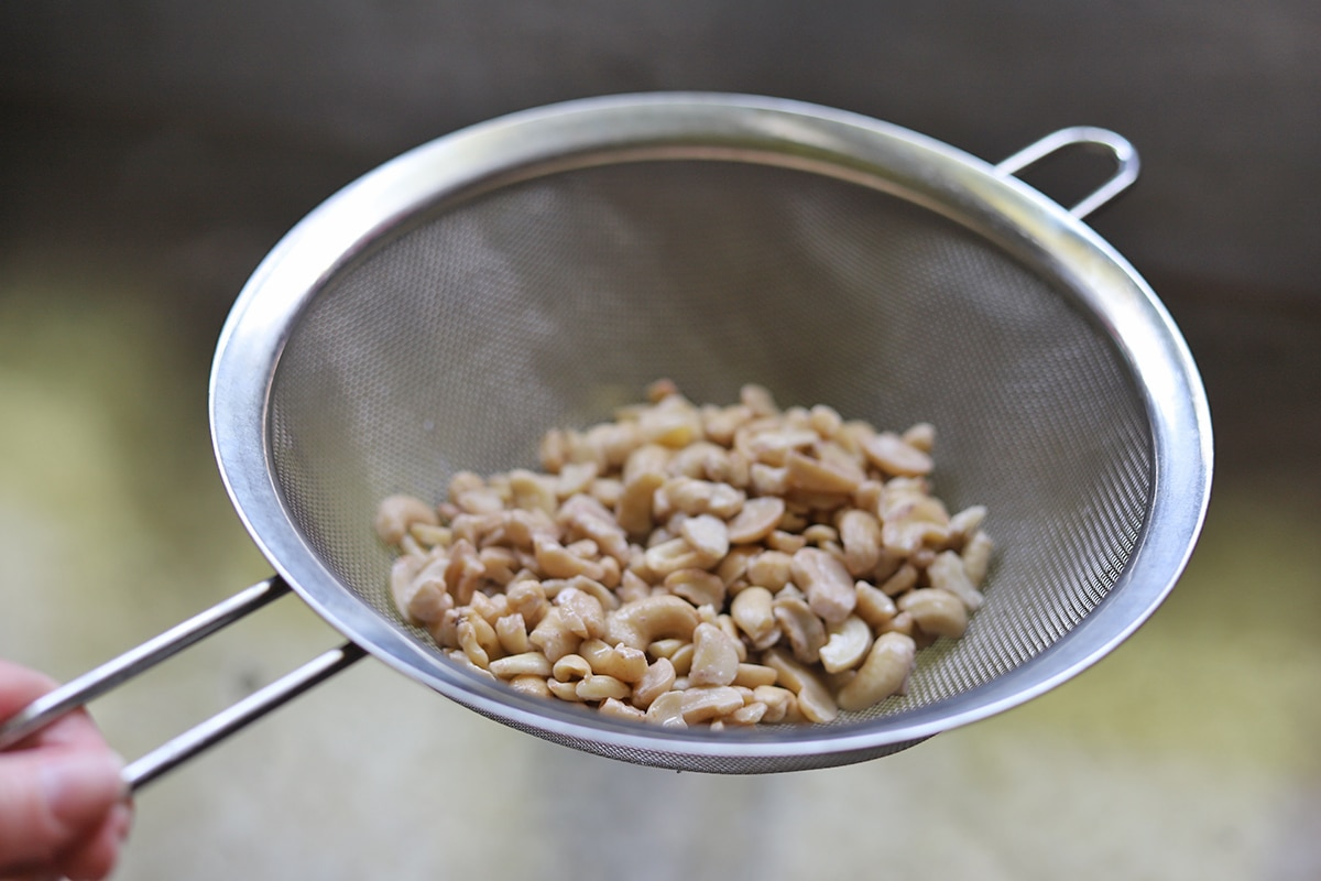 Drained raw cashew pieces in sieve.