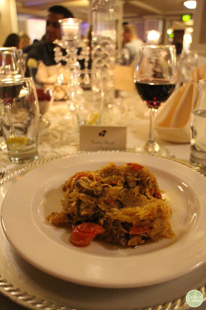 Spaghetti squash on plate with wine in background at wedding reception.