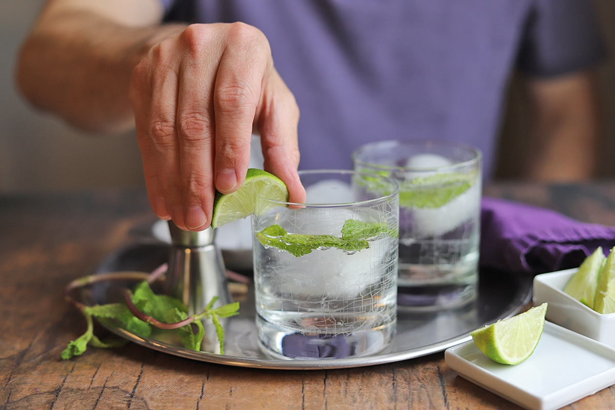 Hand swiping lime wedge around rim of gin and tonic drink.