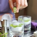 Text overlay: The perfect gin and tonic. Hand squeezing lime into drink.