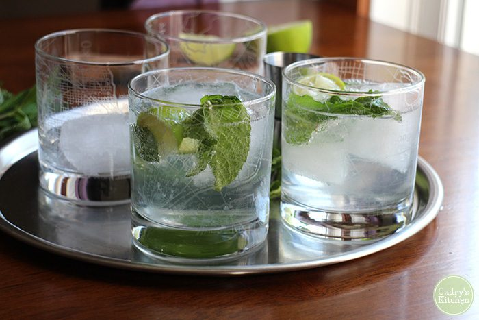 Glasses of gin and tonic on metal tray.