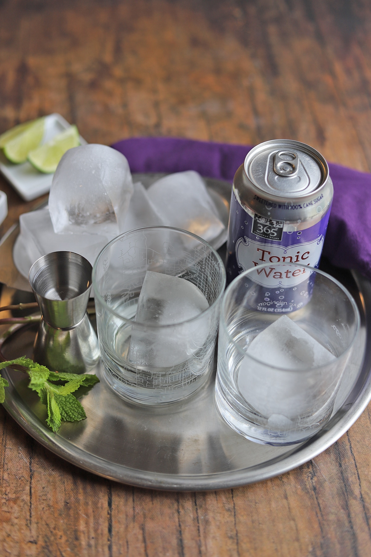 Glasses with ice cubes on tray by mint leaves, gin, lime wedges, and can of tonic water.