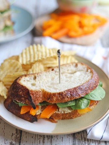 Vegetable sandwich on plate with chips.