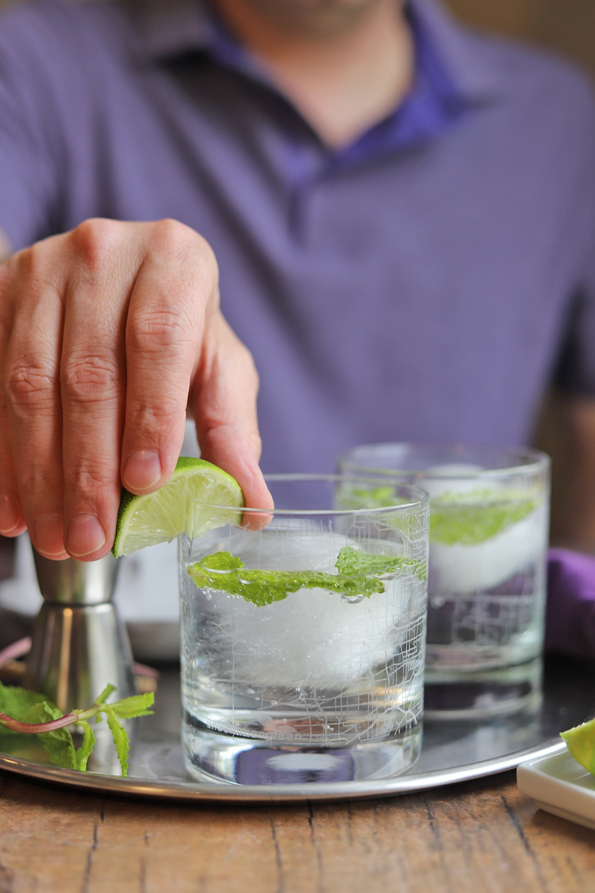 Fingers swiping lime wedge around rim of cocktail glass.