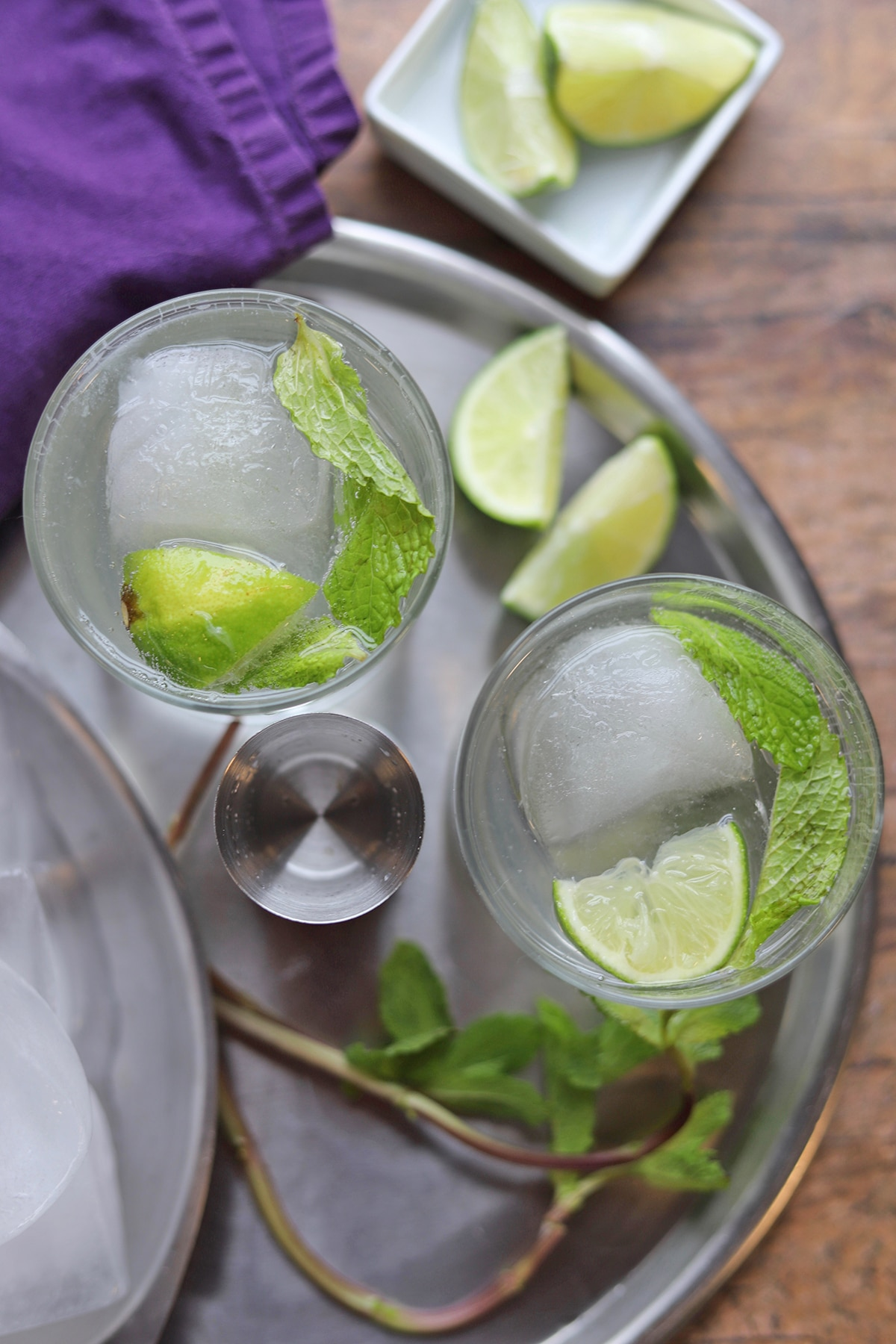 Overhead try with cocktails, lime wedges, and gin.