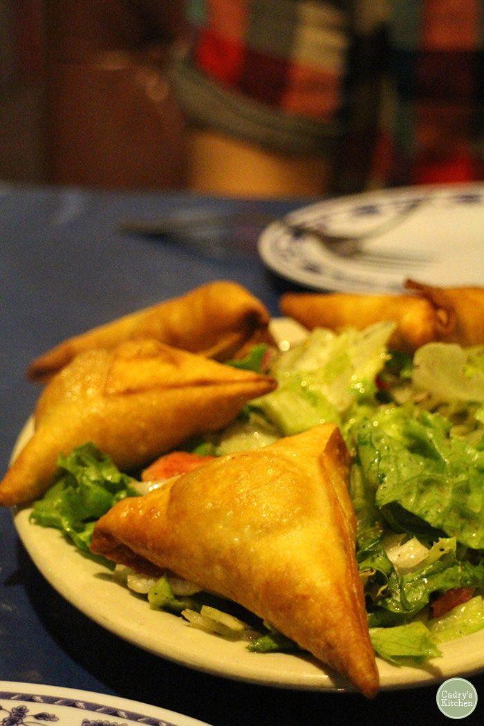 Sambusa on platter with lettuce.