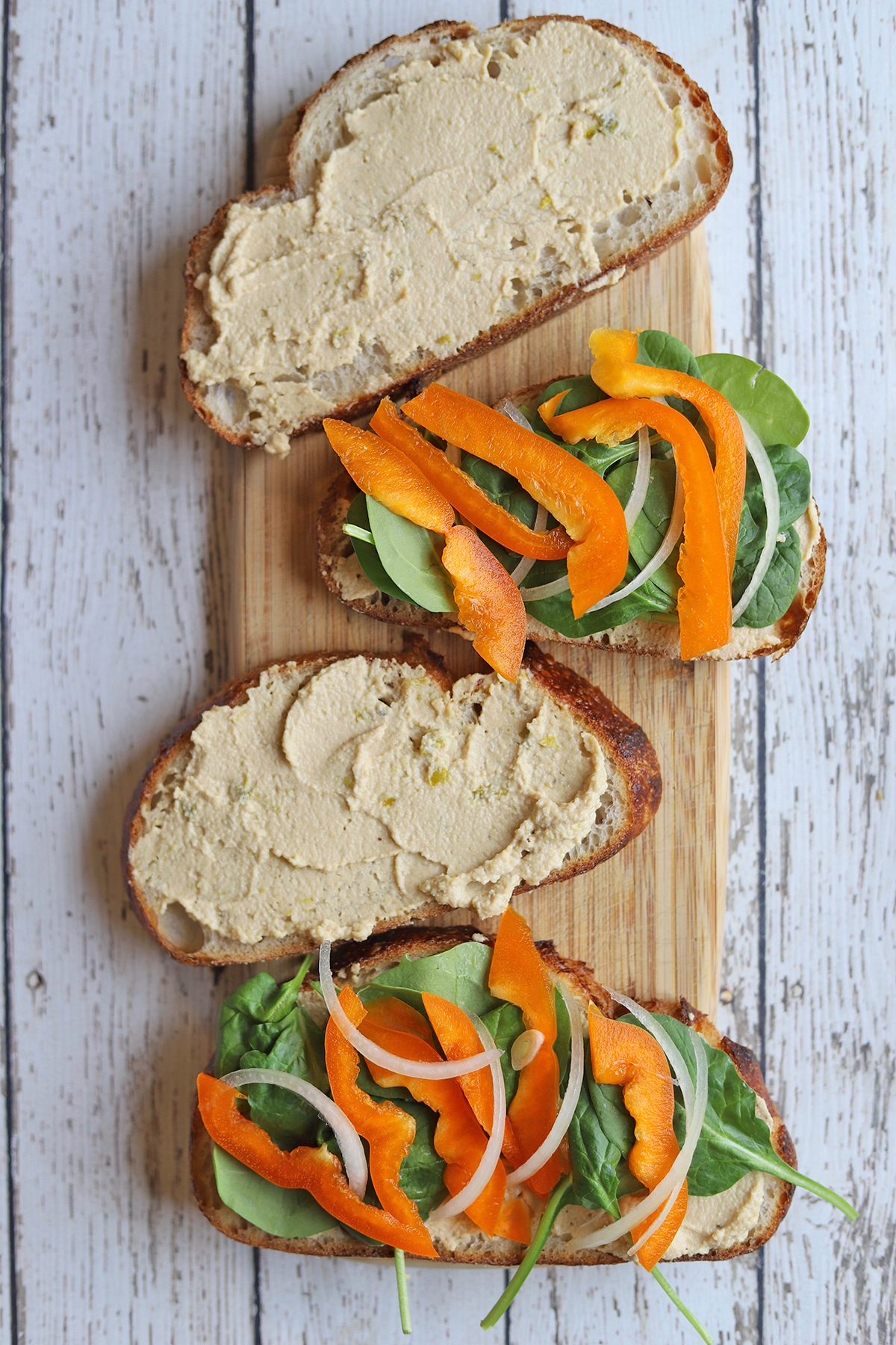 Bread slathered with jalapeno cashew cheese and sliced vegetables.