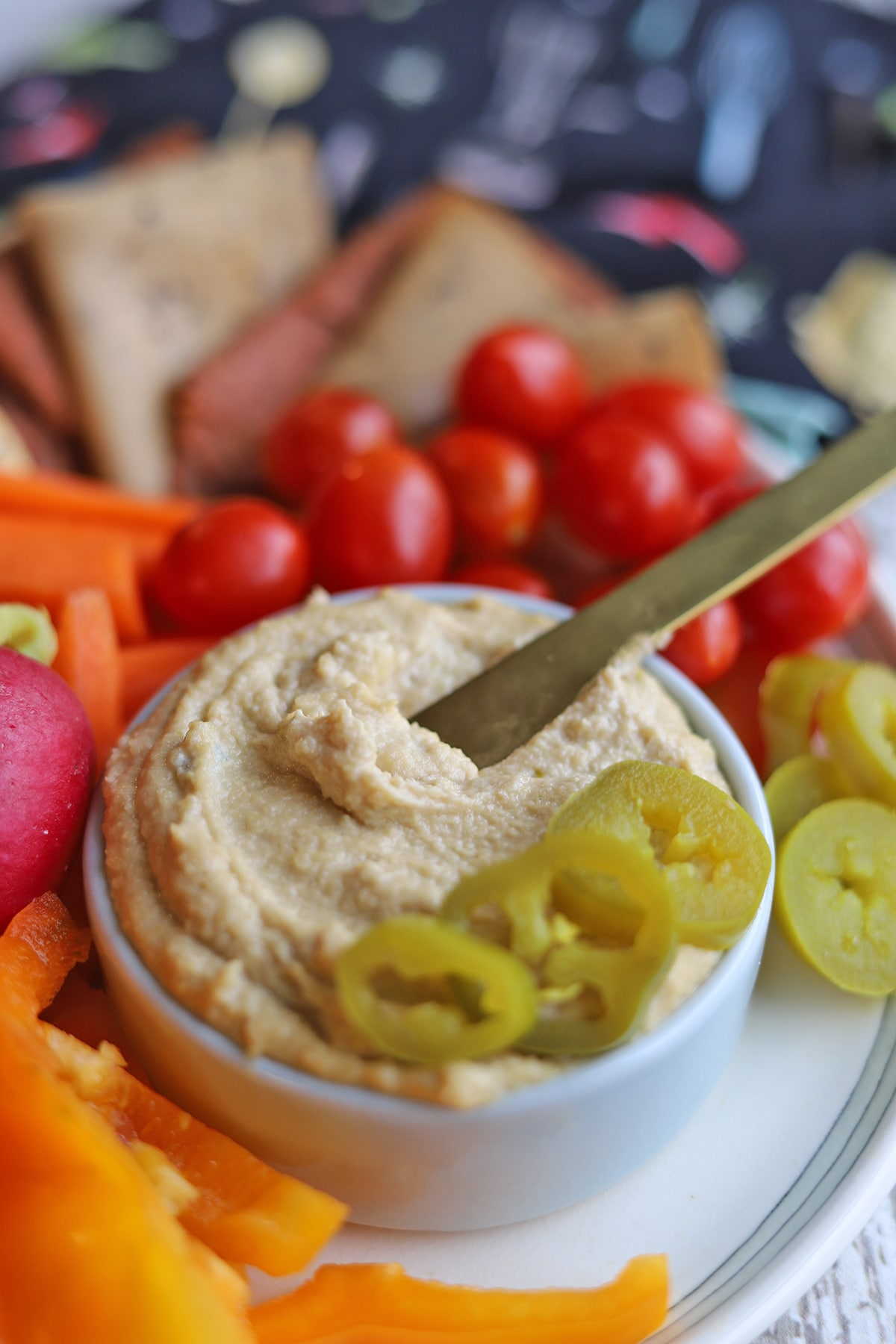 Knife in jalapeno cashew cheese spread on platter.