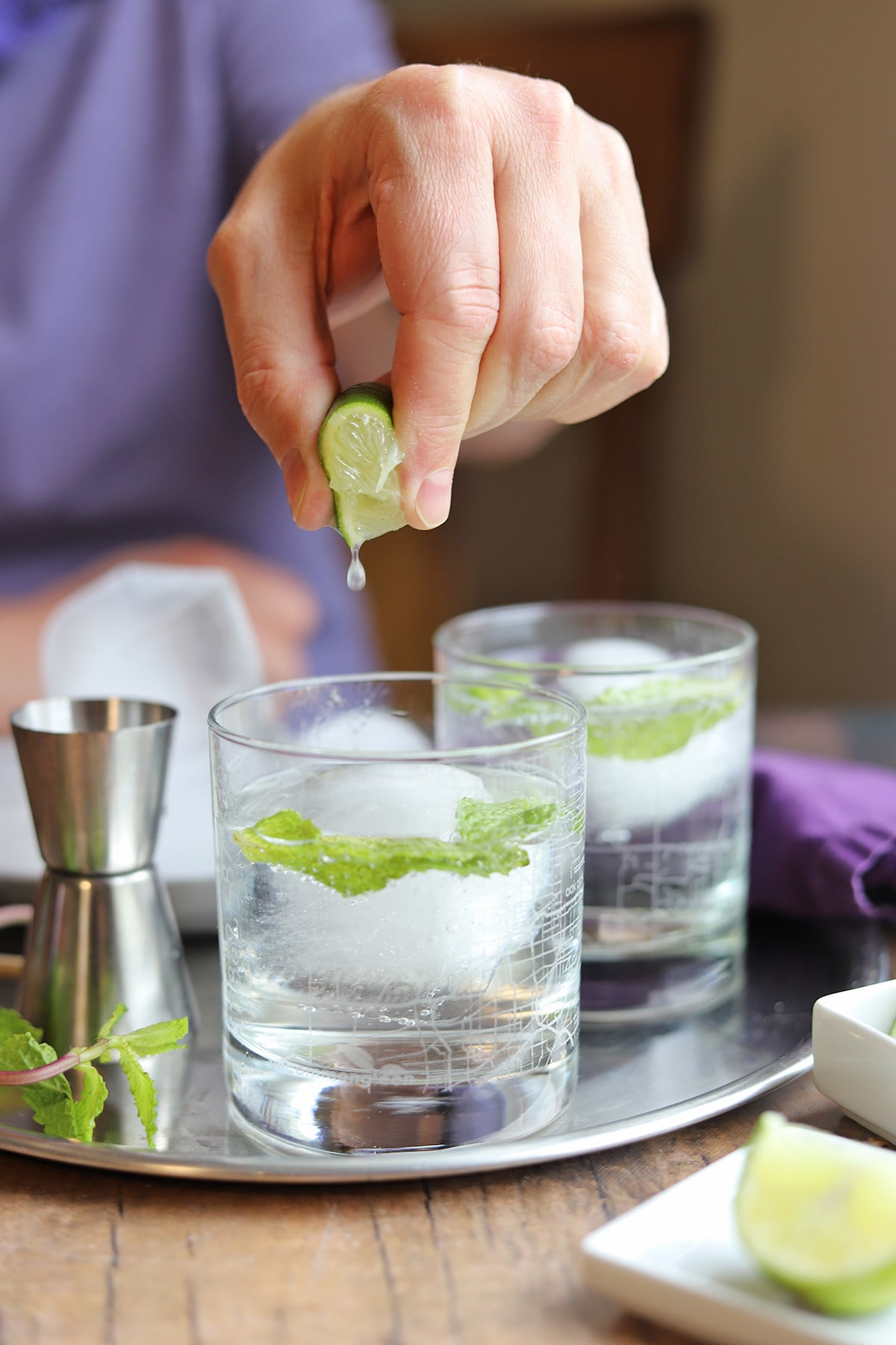 Fingers squeezing lime over gin and tonic with mint.