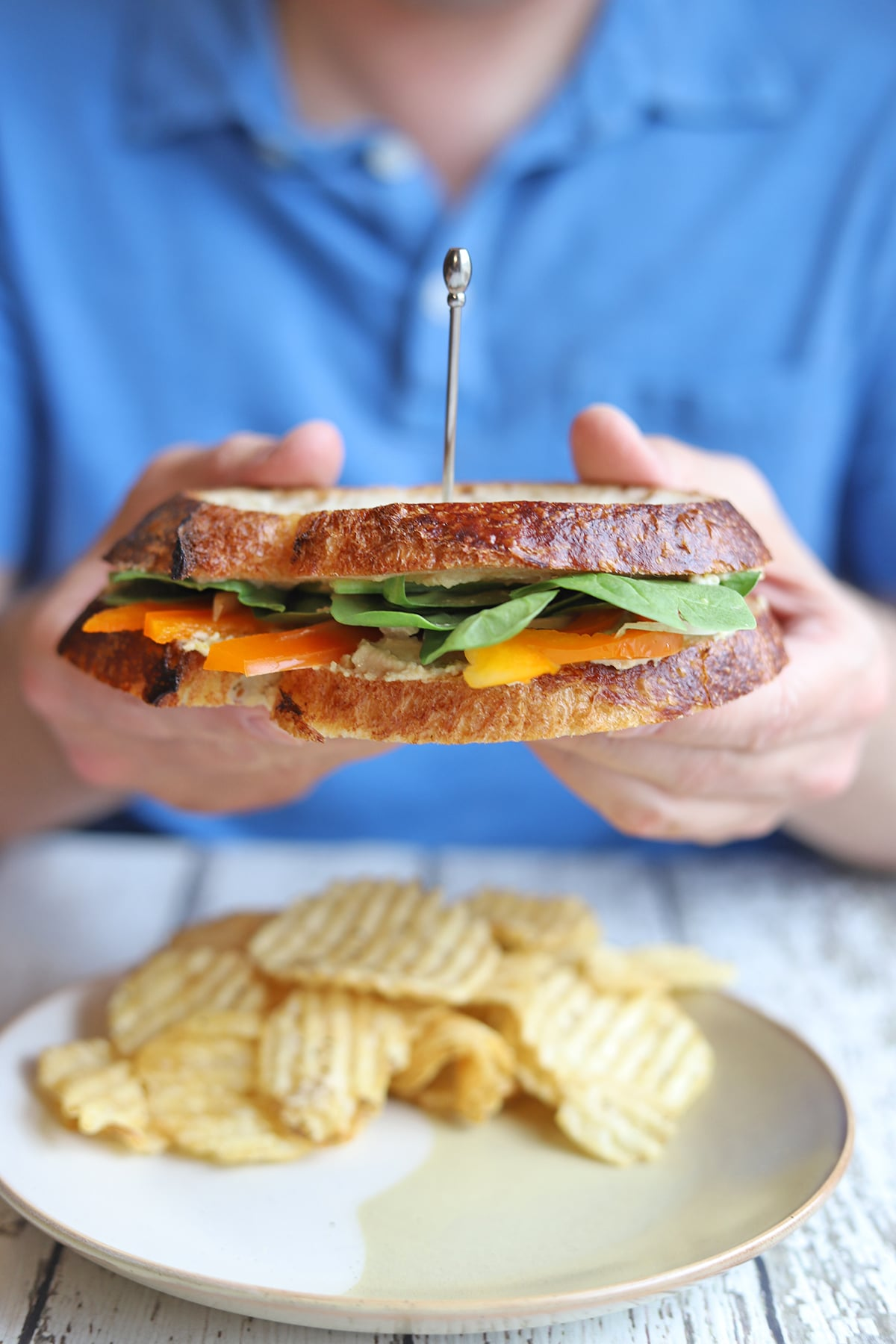 Hands holding vegetable sandwich over plate.