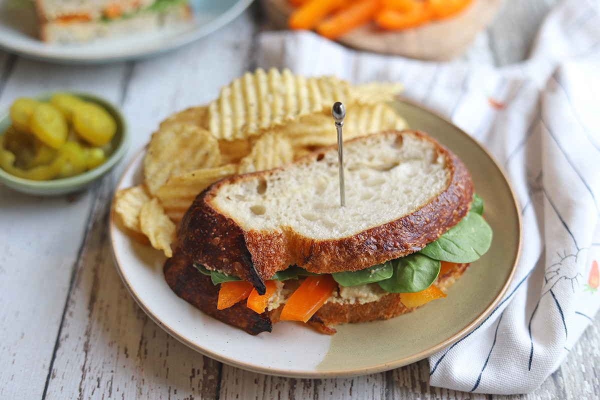 Vegetable sandwich on plate with potato chips.