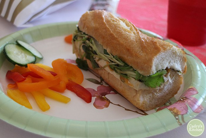 Sandwich on paper plate with bell peppers, cucumbers, and carrots.