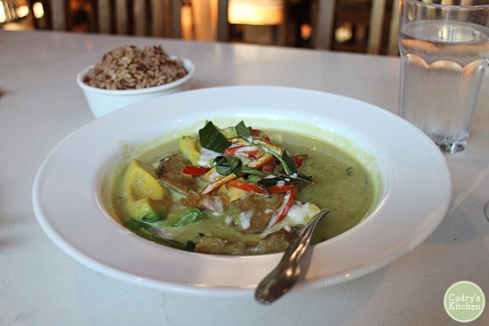 Avocado curry in bowl with brown rice.