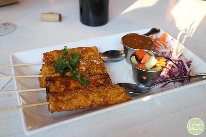Tofu satay on plate with cucumber salad.