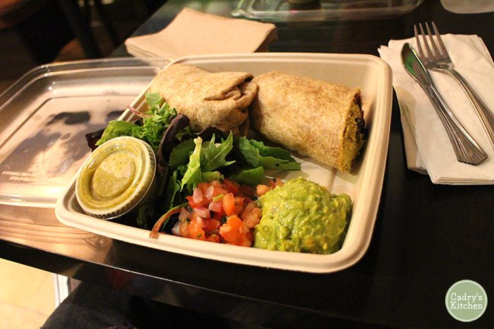 Breakfast burrito with guacamole and salsa.