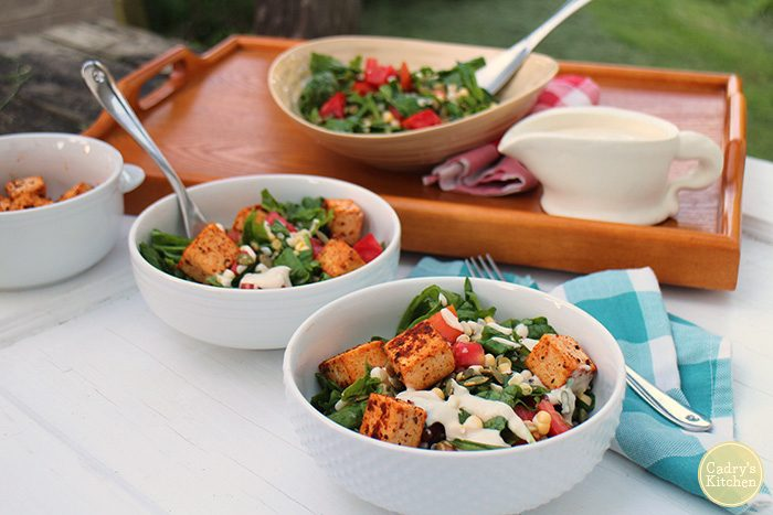 Salad with creole tofu and jalapeno dressing in white bowls.