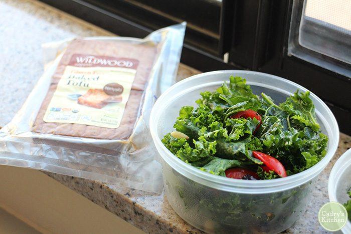 Kale salad in plastic tub. Wildwood baked tofu in packaging.