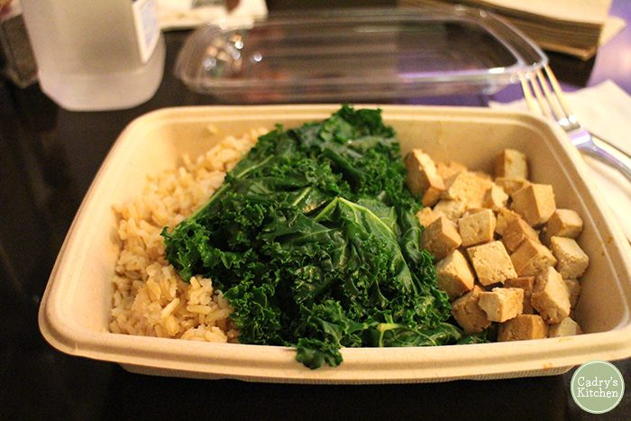 Brown rice, steamed kale, and marinated tofu in to-go container.