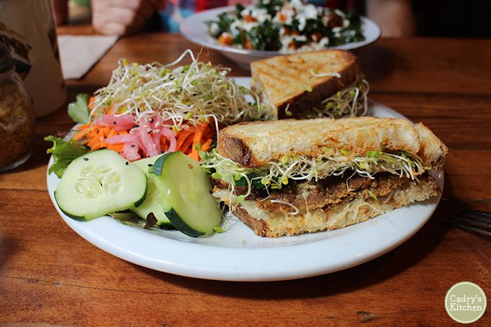 Reuben sandwich with sprouts and cucumbers.