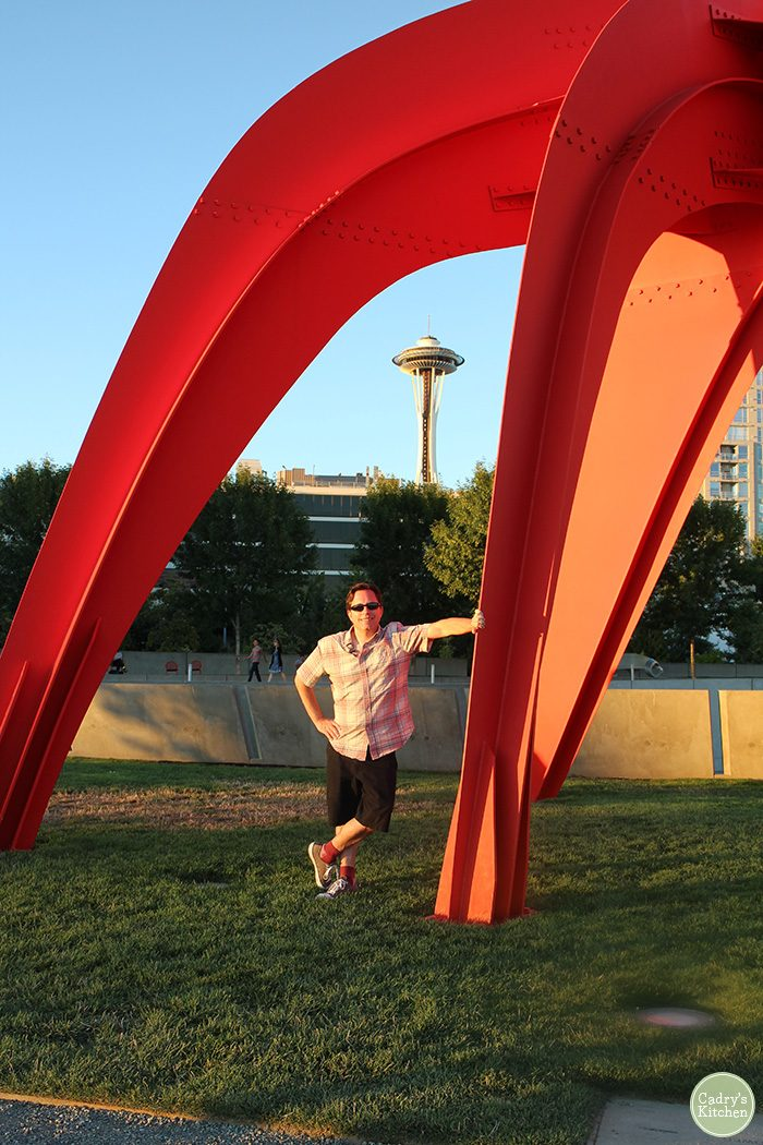 David leaning against sculpture with Space Needle in background.