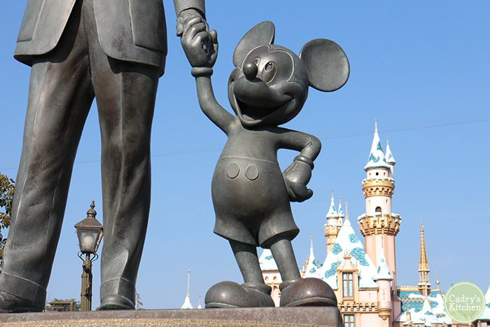 Statue of Mickey Mouse holding Walt Disney's hand in front of castle in Disneyland.