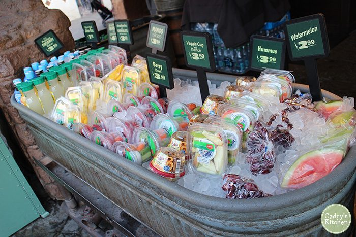 Ice chest at Disneyland with packaged fruit, juices, and hummus.