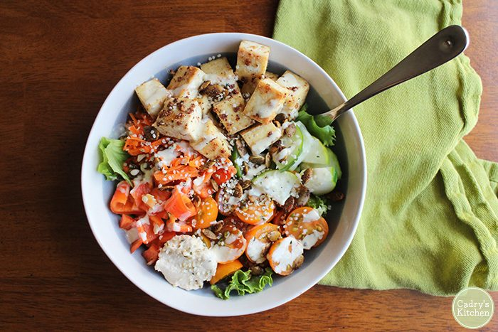 Salad with tofu in bowl by green napkin.