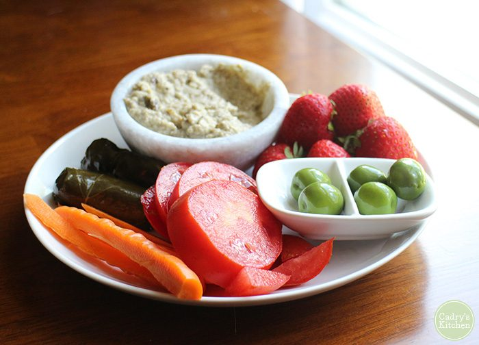 Hummus in bowl by dolmas, tomatoes, carrot sticks, strawberries, and Castelvetrano olives.