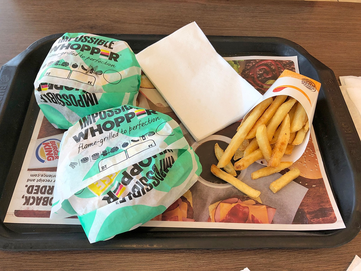 Impossible Whoppers and fries on tray at Burger King.