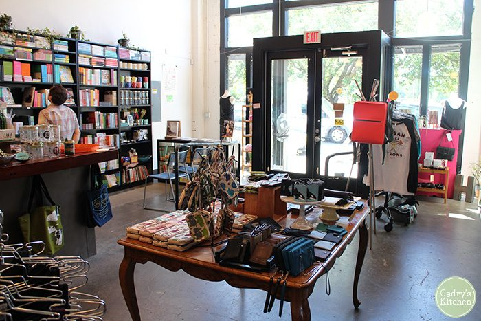 Interior Herbivore Clothing store - wallets, books, and shirts on table.