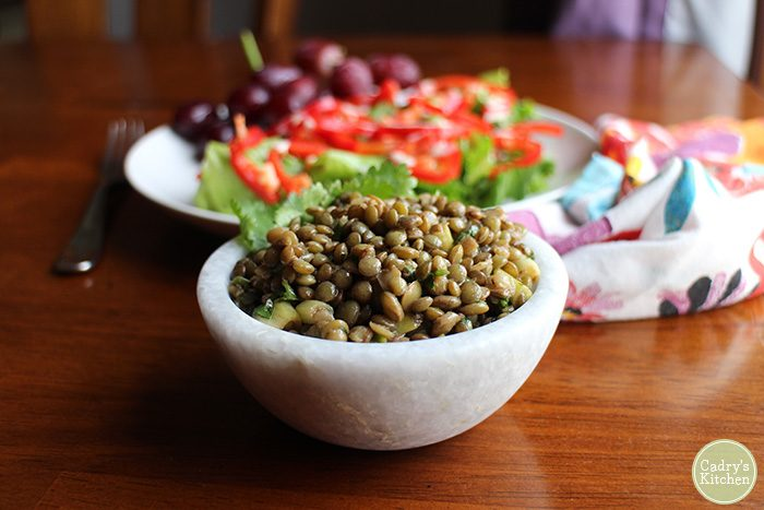 Marinated lentils in stone bowl. Salad in background.