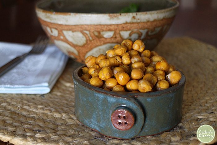 Roasted chickpeas in blue bowl with napkin in background.