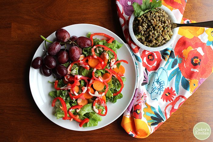Overhead salad with red bell peppers & grapes, colorful napkin, and marinated lentils.