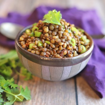 Marinated lentils in bowl on table with cilantro.