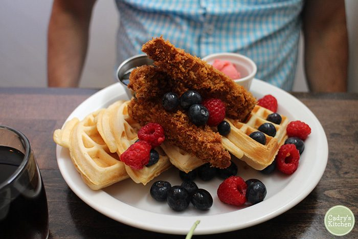 Vegan chicken & waffles with berries on plate.