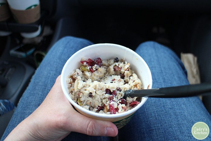 Starbucks oatmeal in paper bowl in lap.