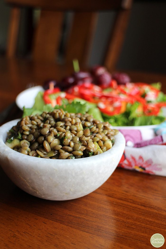 Close-up marinated lentils in stone bowl.