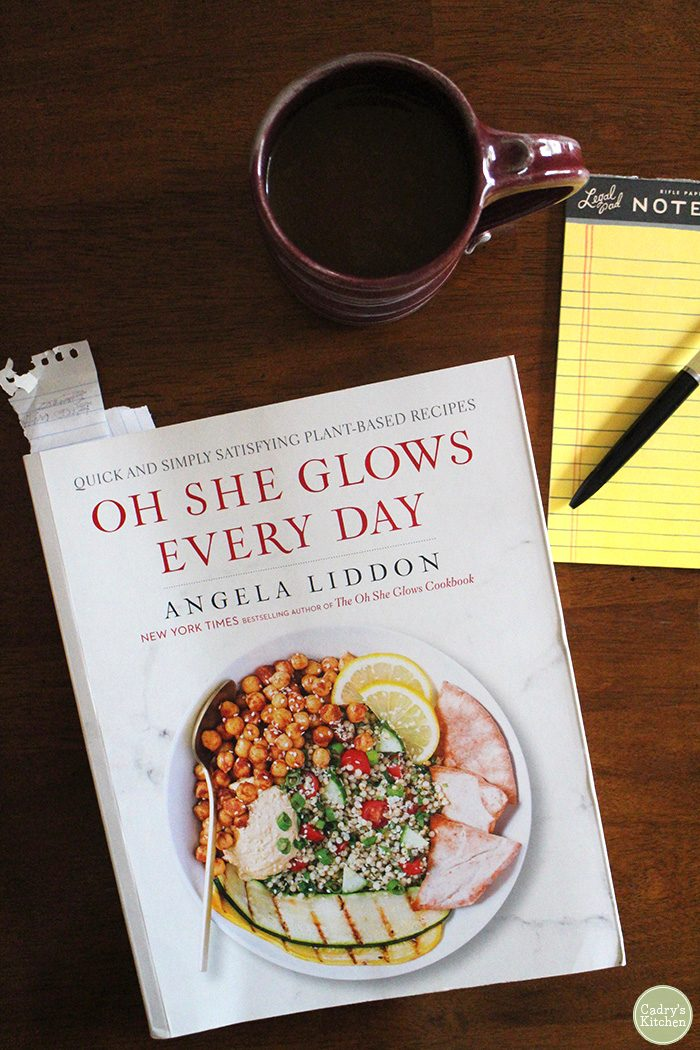 Oh She Glows Every Day cookbook on table with coffee cup & notepad.