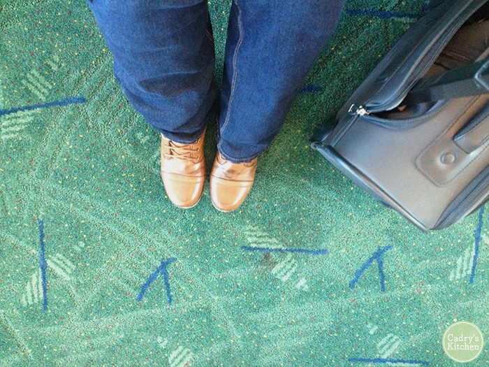 Shoes & suitcase on carpet at Portland Airport.