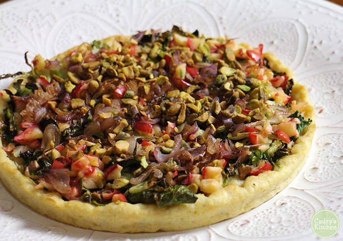 Roasted Brussels Sprouts pizza on a cornmeal crust with apples, caramelized onions & pistachios. It's a true taste of fall. Vegan. | cadryskitchen.com