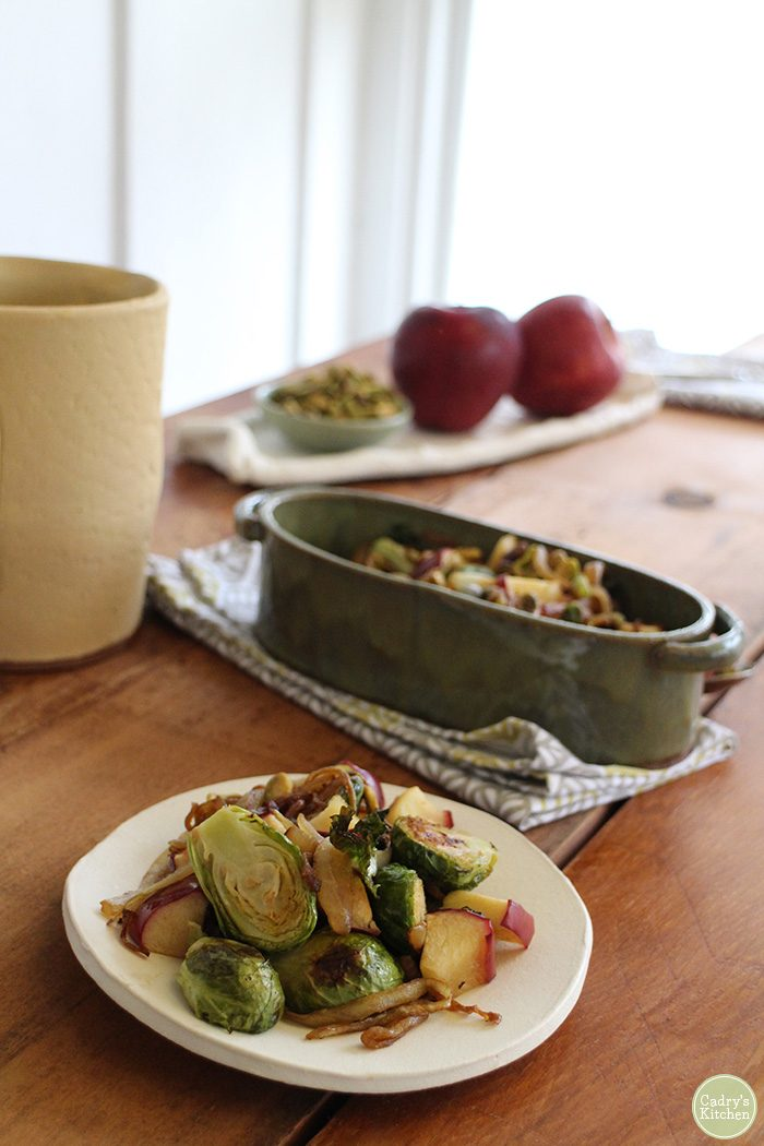 Roasted Brussels sprouts on a plate with apples and pistachios.