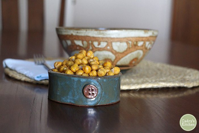Roasted chickpeas in blue bowl on table.