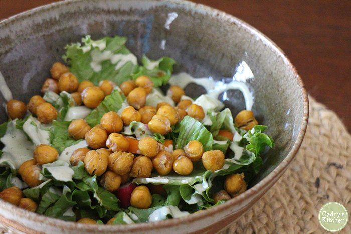 Roasted chickpeas on lettuce salad in bowl.