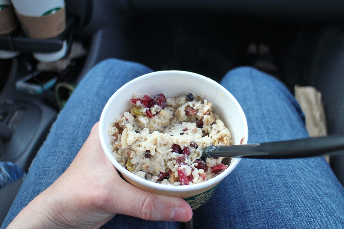 Oatmeal in cup from Starbucks in lap.