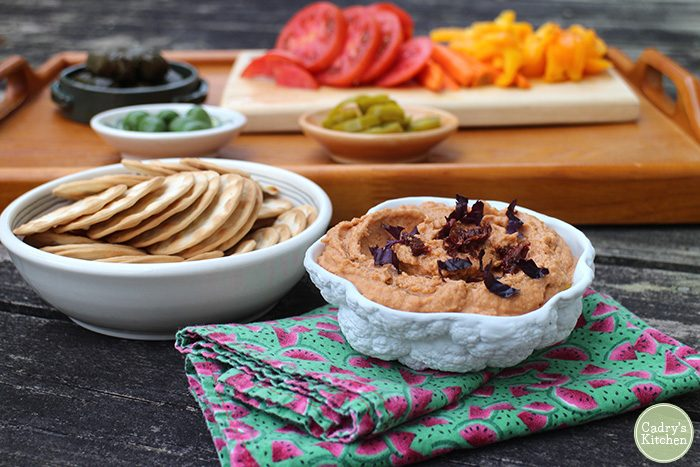 Hummus in bowl by crackers and sliced vegetables.