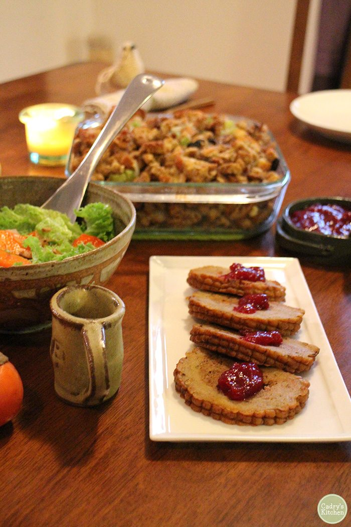 Vegan holidays roast with stuffing, salad, and cranberry sauce.